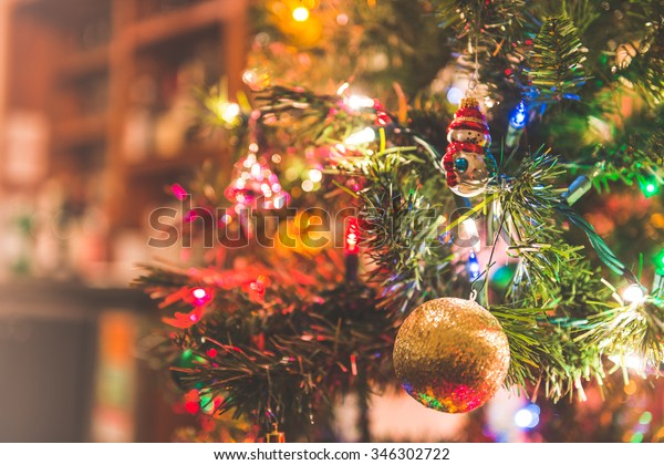 Christmas tree with many ornaments with led lighting bulb.