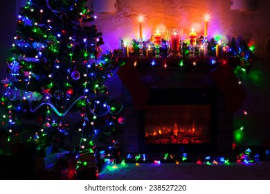 Christmas tree near fireplace in decorated room