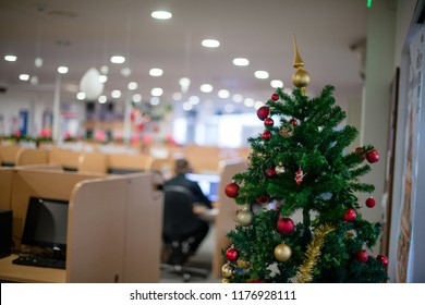 Christmas tree in office, in background man working at his desk.