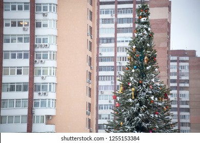 Christmas tree on the background of urban high-rise buildings