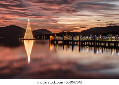 Christmas tree on Lake Woerthersee during colorful sunset. Austria, Carinthia .