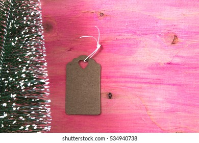 Christmas tree on pink wooden background with  label