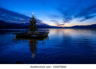 Christmas tree on a pontoon, floating on lake Woerthersee in Austria. Freeze action - ripples visible on lake.