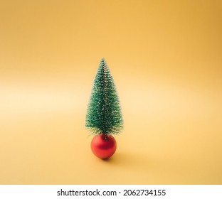 Christmas tree on a red bauble. Minimal concept and design. Yellow gold background.