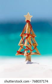Christmas tree on white sandy beach with background ocean blur.