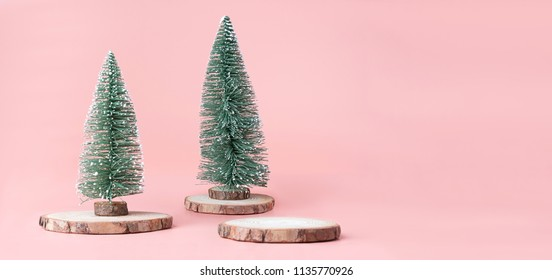 Christmas tree on wood log slice with present box on pastel pink studio background.Holiday festive celebration greeting card with copy space for display of design or content