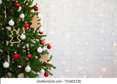 christmas tree over white brick wall with shiny lights