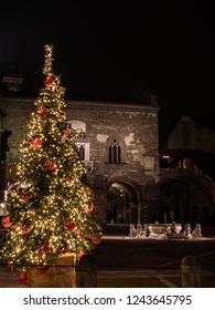 Christmas tree in Piazza Vecchia, in the background the illuminated Contarini fountain, a nocturnal nocturnal image in Bergamo