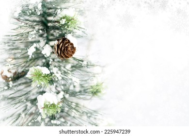 Christmas tree with pine cones, snow and Christmas lights in background. Subtle snowflake  and frosty border. Room for copy space.