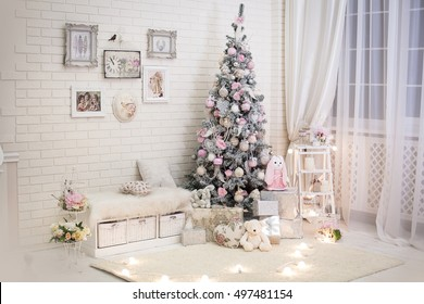 Christmas tree in pink shabby chic style at the white brick wall background. Vintage clock and retro pictures on the wall. New year background.