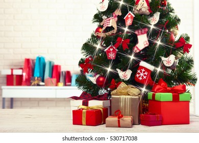Christmas tree with present boxes over white brick wall