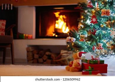 Christmas tree with presents at decorated fireplace. Family celebration of winter holidays. Living room interior with open fire place and Xmas tree with gifts for kids.