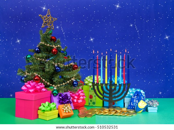Christmas tree with presents next to Hanukkah menorah burning candles, dreidel, chocolate gold coin gifts. Many multi faith families celebrate both Xmas and Hanukkah. This year they are both Dec 25