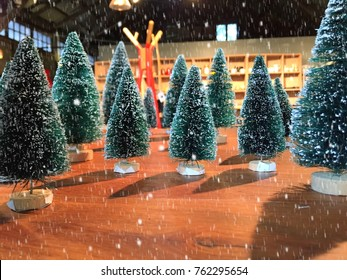 Christmas tree prop in the snow falling on wooden table for Christmas and new year celebration