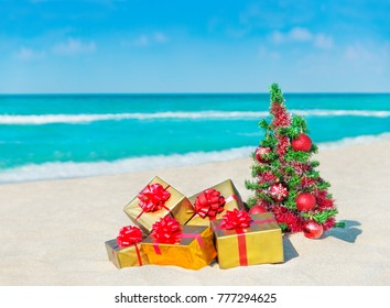 Christmas tree with red balls and golden fancy gift boxes with bows at tropical sandy beach against ocean. New Year holidays in hot countries concept, square greeting card with space for your text