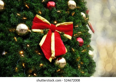 Christmas tree with red bow and with blurred background