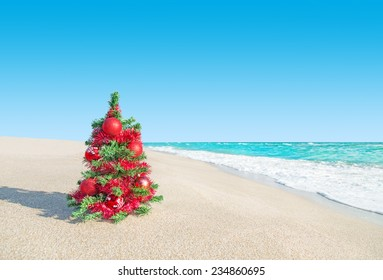 Christmas tree with red decorations at sea beach. New Years vacation concept.