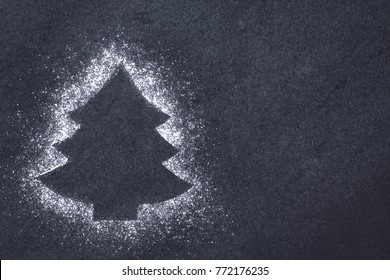 Christmas tree shape formed by powdered sugar on slate, Christmas concept with copy space on the side