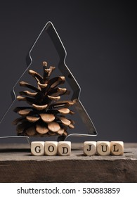 Christmas tree shape with pine cone and wooden dices with the words God Jul, Scandinavian Merry Christmas
