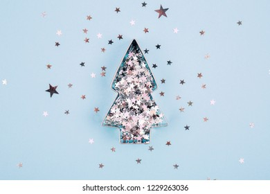 Christmas tree shape with sparkles inside it on blue pastel background. Flat lay style. Concept of celebrating new year. Christmas mood.