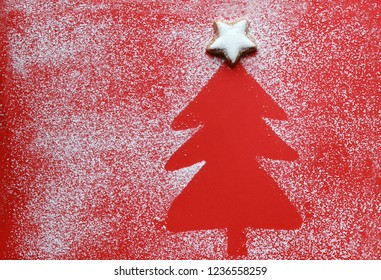 Christmas tree silhouette on red paper with a cinnamon star cookie on top, icing sugar as snow