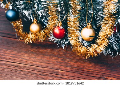 Christmas tree with small colorful balloons. Beautiful Christmas card with a green Christmas tree and frosted balls and shiny gold tinsel.