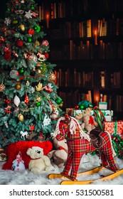 The Christmas tree stands near hobbyhorse