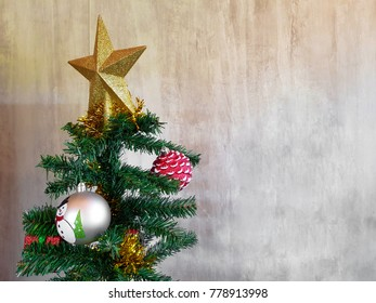 christmas tree with star and ball decoration on cement wall