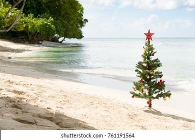 Christmas tree with star on top and baubles planted on the sand of a sunny beach