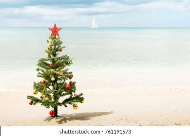 Christmas tree with star on top and baubles planted along a beach with ocean and sailboat in background