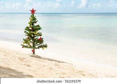 Christmas tree with star on top and baubles standing by a sunny beach