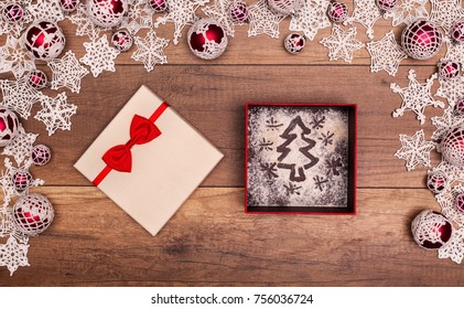 Christmas tree and stars in a gift box - inside seasonal decorations frame on wooden table