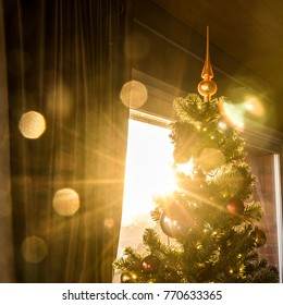 A Christmas tree topper with backlight from the sun shining through the window on a nice winter day. The spike glows because of the sunlight. A romantical, magical and beautiful scenery of Christmas.