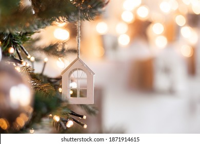 Christmas tree toy in the form of a house on a branch. Christmas mood background. Vacation atmosphere. Comfort hyuge concept cozy. Family budget Mortgage buying real estate