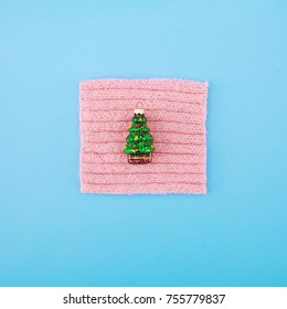 Christmas tree toy on wool and pastel background. Top view. Minimal christmas concept.