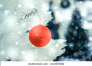 Christmas tree toys decorations and snow-covered Christmas tree branches close-up with snowfall, falling snowflakes, spots white color. Winter Christmas New Year background.
