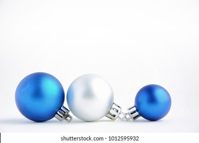 Christmas tree toys on a white background. Christmas decorations on a white surface. Balls and garland of blue and silver colors on table.