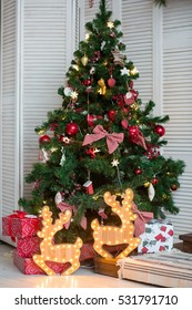 Christmas tree with toys and two illuminated deer. Green tree decorated with colorful toys. Under the tree there are two lighted deer and a lot of boxes with gifts.