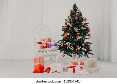 Christmas tree in white interior with stocking-stuffers