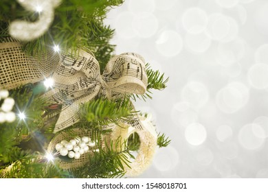 Christmas tree white and tan decoration tied burlap bow with lights and bokeh