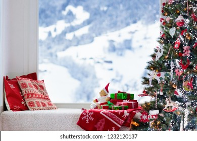 Christmas tree at window with view to snow and Swiss Alps mountains in winter. Decorated living room with Xmas gifts and presents for kids, pillows and toys. Family home seasonal interior decoration.