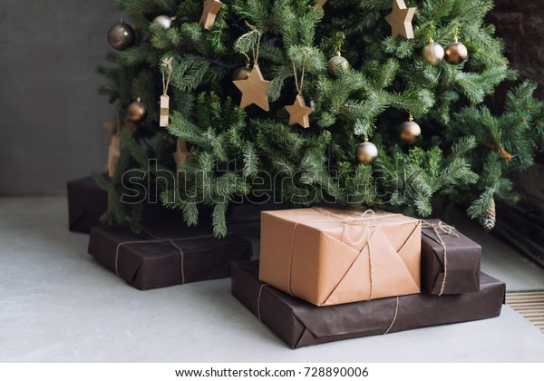 Christmas tree with wooden rustic decorations and presents under it in loft interior.