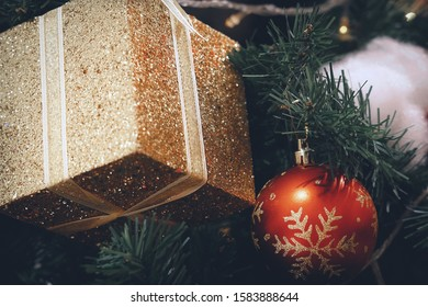 Christmas Trees & Decorations. Red bauble and golden gift box hanging from Christmas tree.