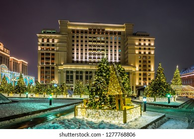 "Christmas trees illuminated by garlands and ""Four seasons"" hotel on Manezhnaya square in winter night. Moscow, Russia."