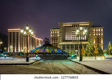 "Christmas trees illuminated by garlands on Manezhnaya square and ""Four seasons"" hotel in winter night. Moscow, Russia."