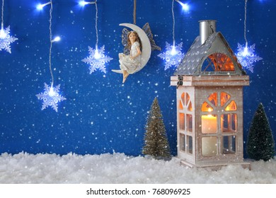 Christmas trees, old lantern, snowflakes silver garland light, fairy on the moon over the snow and blue background