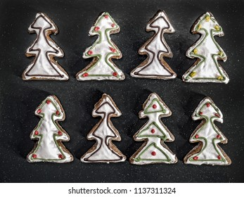 Christmas tree-shaped gingerbread cookies with white icing shot from above over black