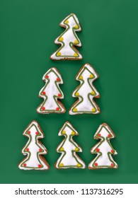Christmas tree-shaped gingerbread cookies with white icing shot from above over green background