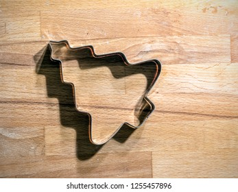 Christmas tree-shaped metal cookie cutter on wooden board