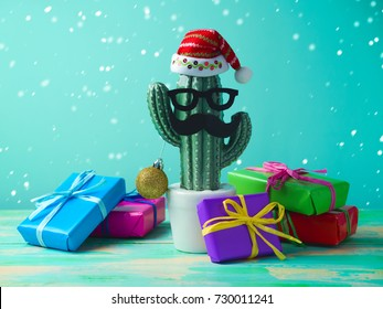 Christmas in tropical climate concept. Cactus as hipster christmas tree with santa hat and gift boxes